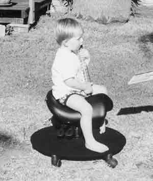 Young child in a Bambach Saddle Seat with a Foot Platform.